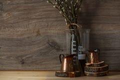 Ainda-vida Rua Ligth os copos de medição de cobre em círculos de madeira com salgueiro ramificam em uma tabela de madeira foto de stock royalty free