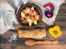 Ainda vida rural Carne cozida com batatas, pão, sal, pimenta e cebola no fundo da tabela de madeira e grosseiro Fotografia de Stock Royalty Free