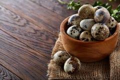 Ainda vida rural com a bacia completa dos ovos codorniz, ovos em um guardanapo homespun, buxo no fundo de madeira, vista superior Fotos de Stock