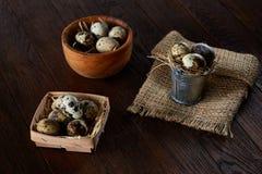 Ainda vida rural com a bacia completa dos ovos codorniz, ovos em um guardanapo homespun, buxo no fundo de madeira, vista superior Fotos de Stock Royalty Free
