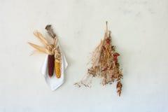 Ainda vida rural, a espiga secou o milho vermelho com um pacote de pimenta vermelha, de grama seca e de pena da galinha pendurand Imagem de Stock