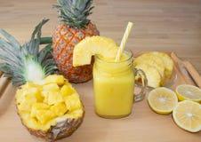 Ainda vida 1 Suco de abacaxi, cocktail com o abacaxi fresco para o café da manhã na manhã em uma bandeja de madeira detox imagens de stock