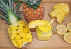 Ainda vida 1 Suco de abacaxi, cocktail com o abacaxi fresco para o café da manhã na manhã em uma bandeja de madeira detox fotografia de stock
