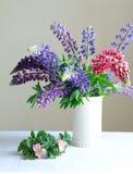 Ainda vida, um vaso branco com roxo e fl cor-de-rosa do lupine e o cor-de-rosa Fotos de Stock Royalty Free