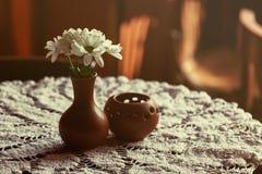 Ainda vida 1 Um vaso marrom da argila com crisântemo está em uma tabela com uma toalha de mesa branca no salão do restaurante Foto de Stock Royalty Free