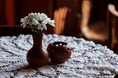 Ainda vida 1 Um vaso marrom da argila com crisântemo está em uma tabela com uma toalha de mesa branca no salão do restaurante Fotografia de Stock Royalty Free