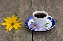 Ainda vida um a xícara de café e uma flor amarela em uma tabela Fotografia de Stock Royalty Free
