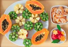 Ainda vida 1 Uma bandeja com papaia, quivi, maçãs Partes de tangerinas e de melancia nas placas fotografia de stock