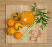 Ainda vida 1 Uma caneca transparente com um punho com suco recentemente espremido da tangerina E tangerinas frescas fotografia de stock royalty free
