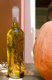 Ainda vida: uma garrafa do azeite, junto com ervas, e pumpki Foto de Stock
