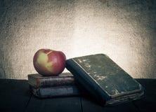 Ainda vida - uma pilha de livros velhos e de maçã na tabela de madeira velha Fotos de Stock Royalty Free