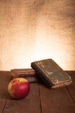 Ainda vida - uma pilha de livros velhos e de maçã na tabela de madeira velha Foto de Stock