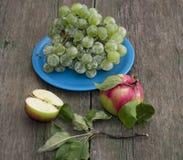 Ainda vida uma placa com uvas e duas maçãs em uma tabela Imagens de Stock Royalty Free