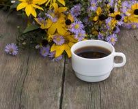 Ainda vida uma xícara de café e umas flores selvagens em uma tabela velha Imagens de Stock Royalty Free