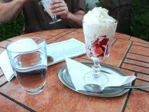 Ainda vida - vidro da água mineral, das morangos com chantiliy e do menu do papel em uma tabela em um restaurante do jardim Fotografia de Stock Royalty Free