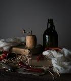Ainda vida, vintage garrafa velha com óleo, pimenta vermelha, moinho, e uma toalha na tabela de madeira Imagens de Stock Royalty Free