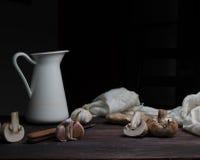 Ainda vida, vintage jarro, faca e cogumelos em uma tabela de madeira escura arte, pinturas velhas Fotografia de Stock