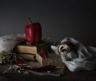 Ainda vida, vintage pimenta vermelha, moinho, e uma toalha na tabela de madeira Foto de Stock Royalty Free