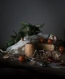 Ainda vida, vintage tomates de cereja, louro, um moinho e uma faca de prata velha na tabela de madeira Foto de Stock