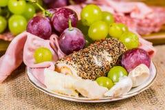 Ainda vida - vista ascendente próxima da uva de muscat amarela e vermelha, do queijo decorado, do alho e do salame em uma placa b Imagem de Stock
