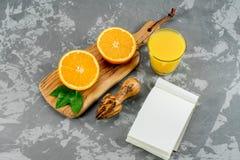 Ainda vidro da vida do suco de laranja e fatias de fruto alaranjado no fundo concreto com bloco de notas Fotos de Stock