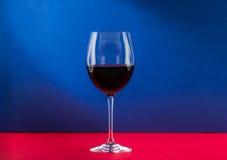 Ainda vidro da vida do vinho com efeito da luz agradável no fundo vermelho e azul Fotografia de Stock Royalty Free