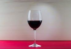 Ainda vidro da vida do vinho com efeito da luz agradável no fundo vermelho e bege Imagem de Stock