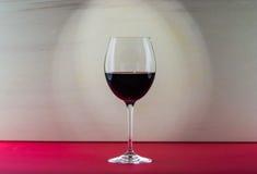 Ainda vidro da vida do vinho com efeito da luz agradável no fundo vermelho e bege Foto de Stock