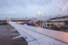 Aindrops på flygplanfönster vid landningsbanan En regnig dag på en flygplatslandningsbana Arkivfoto