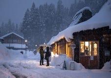 Ainokura, Japon - 30 décembre 2018 : Couples se tenant devant la seule boutique dans ce petit village, se protégeant contre h photos stock