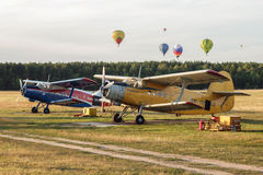 Aiplanes and hot air balloons. Minsk, Belarus - July 18, 2015: Two airplanes AN-2 standing on the ground and some hot air balloons in the air at the air show Royalty Free Stock Photo