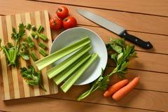 Aipo, cenouras e tomate com faca ao lado Imagens de Stock