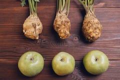 Aipo com raizes e folhas e maçãs verdes no tabl de madeira Imagem de Stock Royalty Free