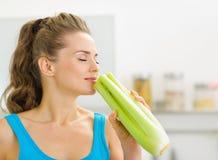 Aipo de cheiro da jovem mulher na cozinha Fotos de Stock