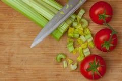 Aipo e tomates em uma placa de corte Imagem de Stock