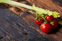 Aipo fresco e tomates crus vegetais no fundo de madeira de Brown Foto de Stock