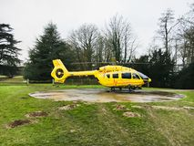 Air ambulance helicopter. Bury St Edmunds, UK - December 4 2017:  A yellow helicopter used by the East Anglia Air Ambulance service on a heipad outside the West Stock Image