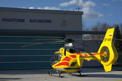 Air ambulance station. Medical helicopter standing on the landing. The helicopter is always ready to depart. The helicopter is yellowish red. The weather is Stock Photo