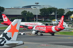 Air Asia and Air Belin Airbus A320 taxiing at Changi Airport Stock Image