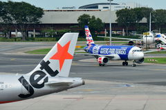 Air Asia Airbus A320 que taxiing ao lado do rival Jetstar Ásia no aeroporto de Changi Imagens de Stock Royalty Free
