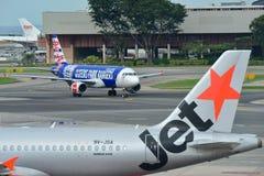 Air Asia Airbus A320 que taxiing ao lado do rival Jetstar Ásia no aeroporto de Changi Foto de Stock Royalty Free