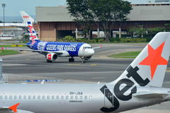 Air Asia Airbus A320 taxiing next to a parked Jetstar Asia Airbus A320 at Changi Airport Royalty Free Stock Photography