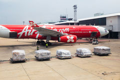 Air Asia airplane waits for luggage cargos to be loaded. BANGKOK, THAILAND - 24 July 2016 - Air Asia airplane waits for luggage cargos to be loaded at Don Mueng Royalty Free Stock Photo