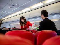 Air Asia, Banguecoque - 22 de novembro de 2018: Alimento e bebidas do saque do aeromoço de Air Asia aos passageiros a bordo fotografia de stock