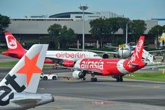 Air Asia e ar Belin Airbus A320 que taxiing no aeroporto de Changi Imagem de Stock