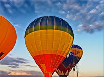 Air balloon flying in the blue sky. Vibrant air balloons float exhibition in the countryside field. Romantic travel transport. Sunset sky with flight vehicle Royalty Free Stock Images