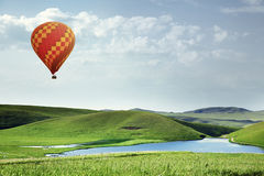 Air balloon flying over the meadows Stock Photo