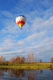 Air balloon taking off. Air balloon taking of near lake shore in autumn royalty free stock image
