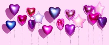 Air balloons. Bunch of purple heart shaped foil balloons, isolated on pink background. Valentine`s day. Background. Wide screen stock photo