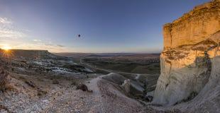 Air baloons at sunrise near big White rock Stock Photo